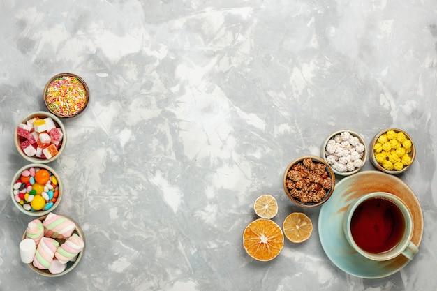Вид сверху на вкусные сладкие композиции из конфет и зефира с чашкой чая на белой поверхности