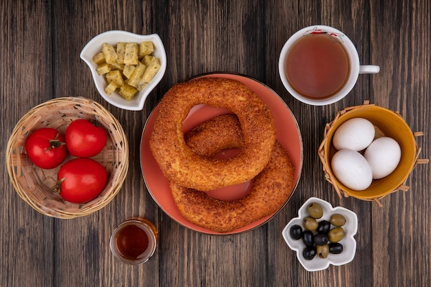 おいしいトルコのゴマベーグルの上面図、ボウルにオリーブ、バケツにトマト、木製の背景にお茶を