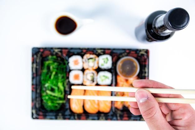 木製トレーにセットされた美味しいバラエティ寿司の上面図。椀にフラマキ、マキ、ロール、握り、海藻、ご飯を入れた日本食のハイアングルビュー。新鮮な日本の寿司のフラットな画像。