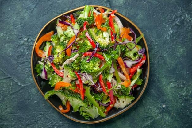 暗い背景にさまざまな新鮮な野菜とプレートのおいしいビーガンサラダの上面図