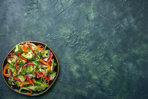 暗い背景の右側にさまざまな新鮮な野菜が入ったプレートのおいしいビーガンサラダの上面図