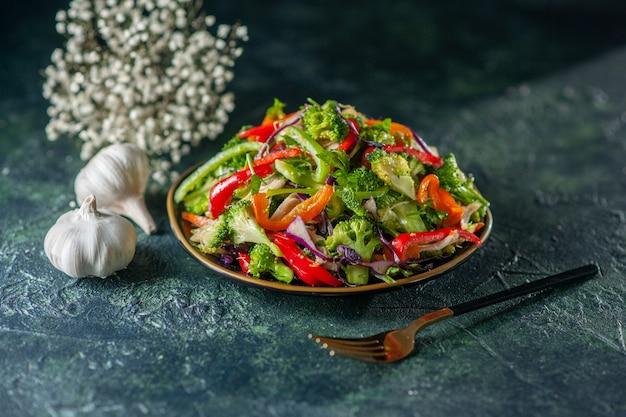 青いぼやけた背景にプレートフォークニンニクの花に新鮮な食材を使ったおいしいビーガンサラダの上面図