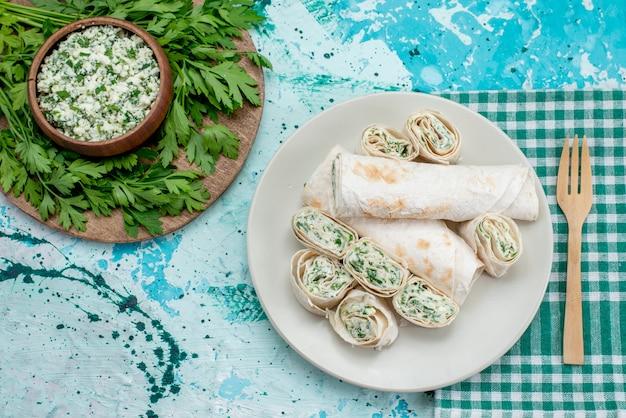 おいしい野菜ロール全体の上面図と青い机の上に緑とサラダでスライス、フードミールロール野菜スナック