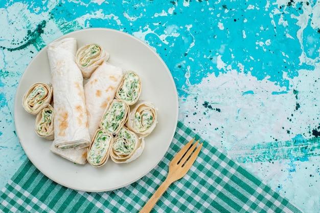 おいしい野菜ロール全体の上面図と明るい青色のフードミールロール野菜スナックに木のスプーンでスライス
