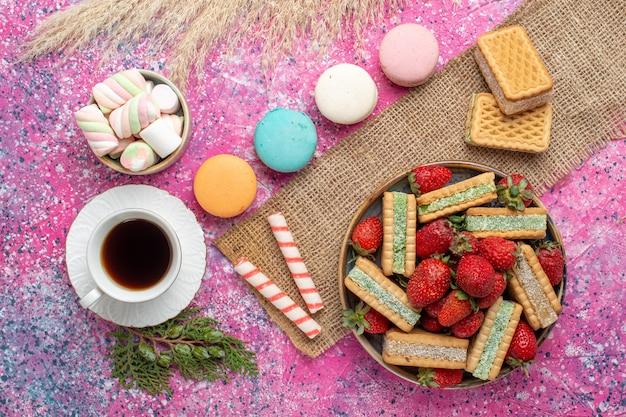 Вид сверху вкусного вафельного печенья с французскими макаронами и чаем на розовой поверхности