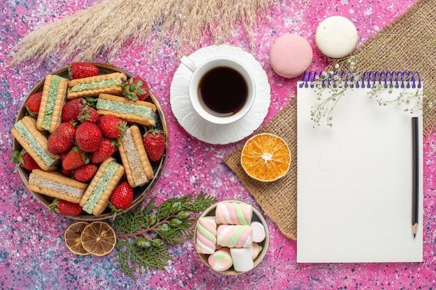 ピンクの表面に新鮮な赤いイチゴとマカロンが付いたおいしいワッフルクッキーの上面図