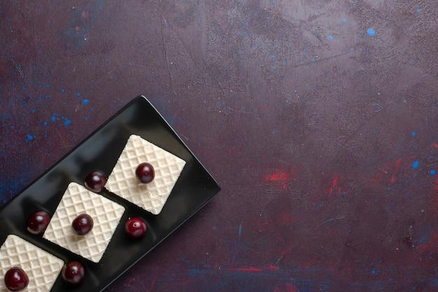 어두운 표면에 접시 안에 체리와 함께 맛있는 와플의 상위 뷰