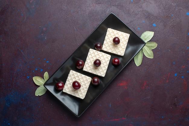 Вид сверху вкусных вафель с вишней внутри тарелки на темной поверхности