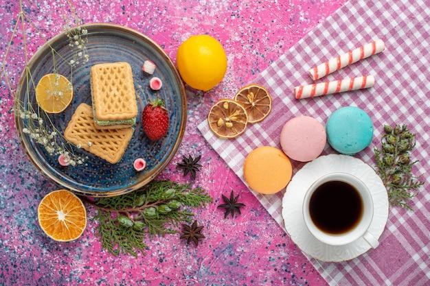 Вид сверху вкусных вафель с чашкой чая и французскими макаронами на розовой поверхности