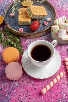 Вид сверху вкусных вафель с макаронами и зефиром на розовой поверхности