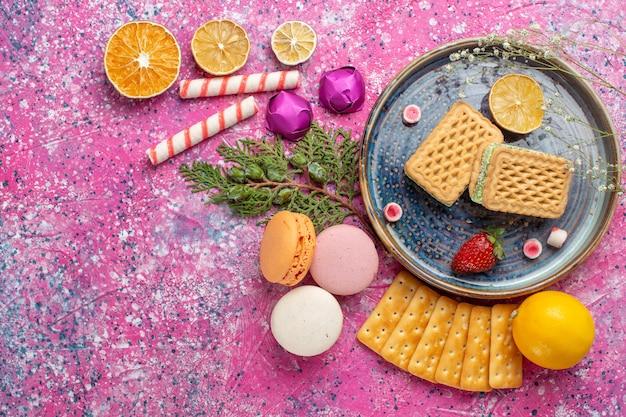 ピンクの机の上にフレンチマカロンとクラッカーとおいしいワッフルの上面図