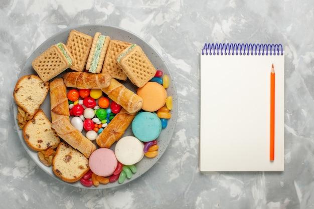 Вид сверху вкусных вафель с кусочками торта macarons и конфетами на белой поверхности