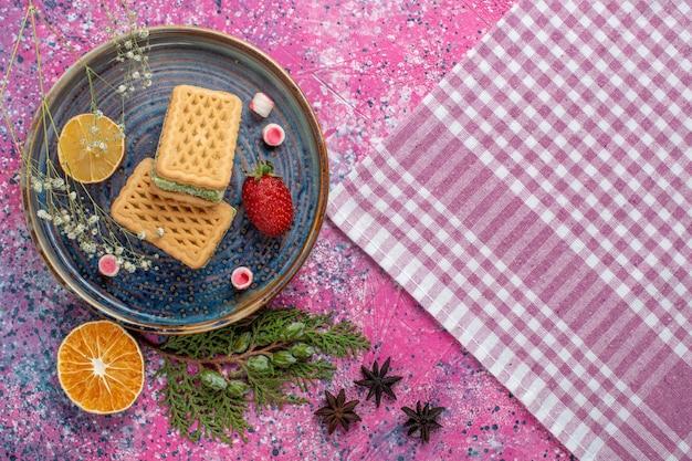 Вид сверху вкусных вафель с клубникой на светло-розовой поверхности
