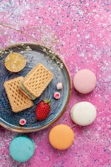 분홍색 표면에 맛있는 프랑스 마카롱과 함께 맛있는 와플의 상위 뷰