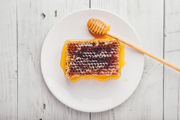 Вид сверху на вкусные вкусные соты на яркой тарелке с ковшом для меда над светлым деревянным