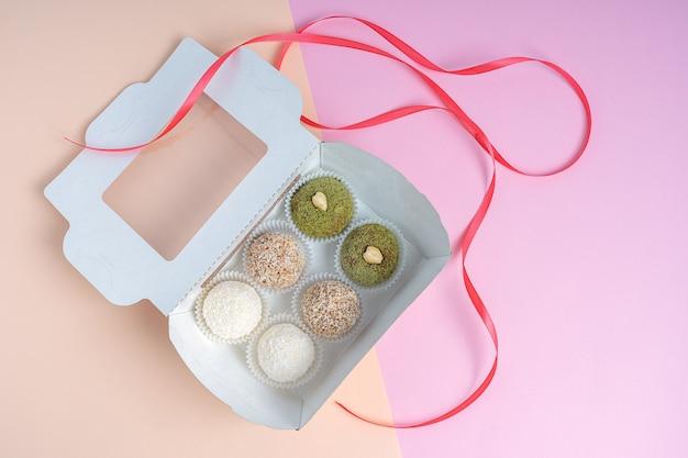 다채로운 배경에 다양한 너트 트뤼플 또는 에너지 공을 가진 배달 판지 상자의 상위 뷰