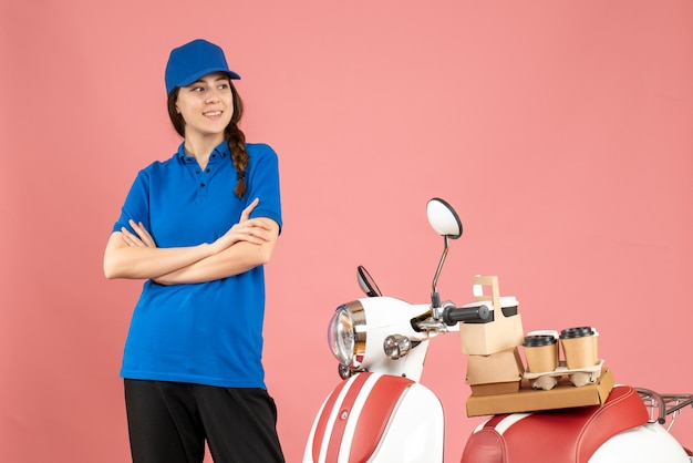 パステル ピーチ色の背景にコーヒーと小さなケーキが付いているオートバイの近くに立っている配達宅配便の女性のトップ ビュー 無料写真