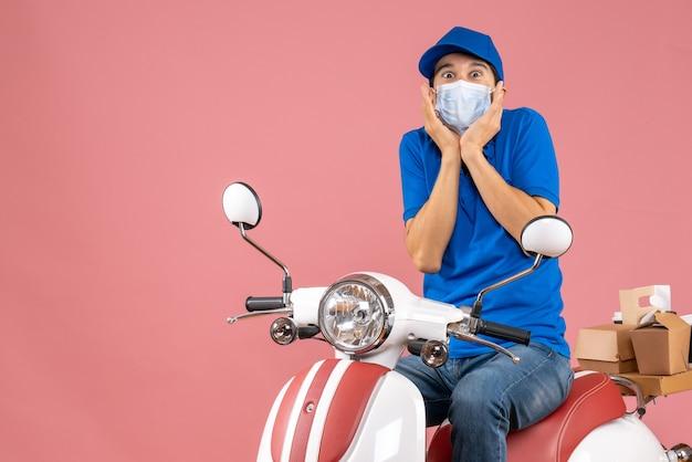 医療用マスクを着た配達員がスクーターに座り、パステル調の桃の背景に驚きを感じている帽子をかぶったトップビュー
