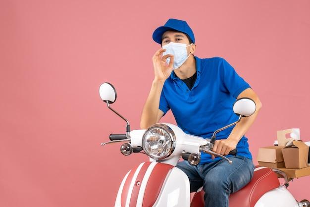 医療用マスクを着た配達員がスクーターに座り、パステル調の桃の背景に完璧なジェスチャーをする帽子をかぶったトップビュー