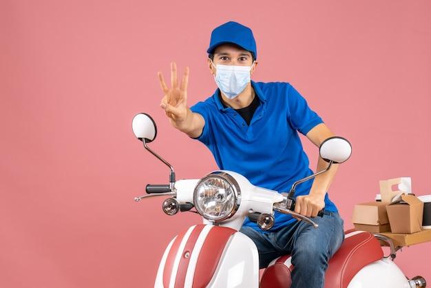 スクーターに座り、パステル調の桃の背景に3つを示す帽子をかぶった医療用マスクの配達員のトップビュー