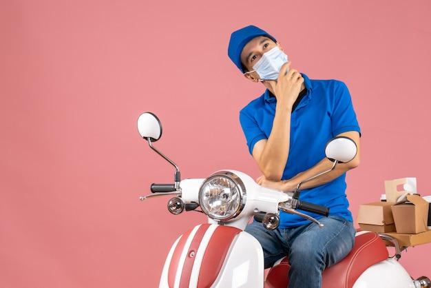 パステル調の桃の背景に深い考えを持ってスクーターに座っている帽子をかぶった医療用マスクの配達員のトップビュー
