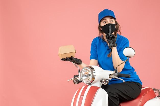医療用マスクと手袋を着た配達員がスクーターに座って注文を配達し、パステル調の桃の背景に沈黙のジェスチャーをするトップビュー