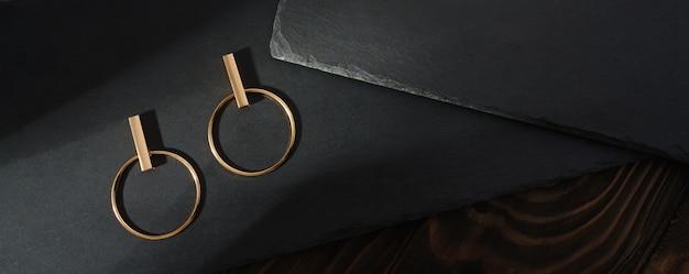 Вид сверху дизайна золотых сережек на черных каменных плитах на деревянной поверхности