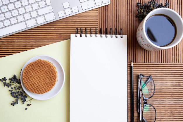 Вид сверху письменного стола с кофе, блокнотом и клавиатурой