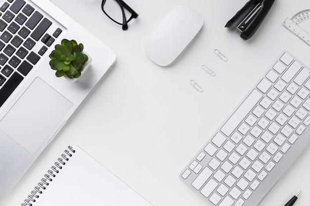 Вид сверху рабочего стола с ноутбуком и клавиатурой