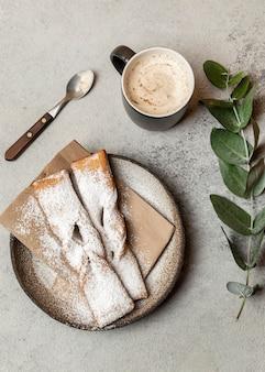 Вид сверху на десерт с сахарной пудрой и кофе