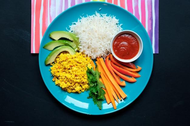 Взгляд сверху диетического кетчупа и овощей с вилкой рядом с голубой тарелкой на белой предпосылке.