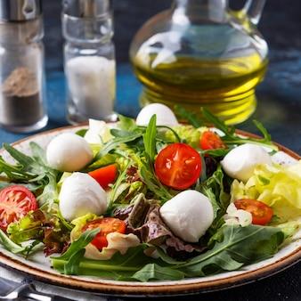 ルッコラ、レタス、チェリートマト、モッツァレラチーズのダイエットサラダの上面図。閉じる