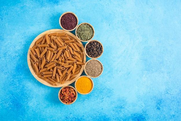 木の板の上のダイエットパスタと青い背景の上のさまざまな種類のスパイスの上面図。