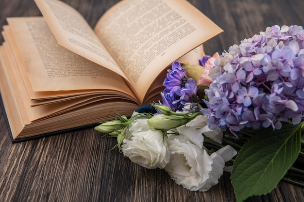 木製の背景にライラックローズデイジーなどのさまざまな美しい花の上面図