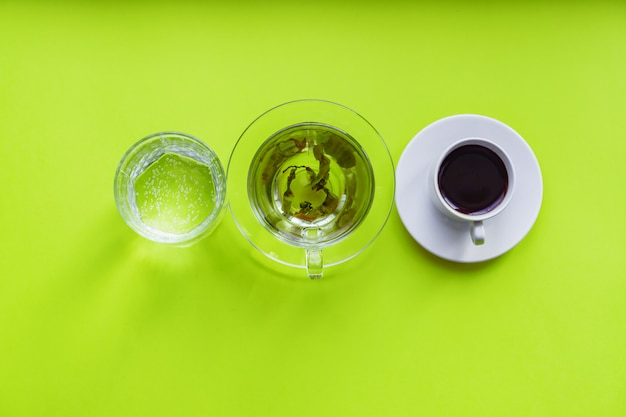 コーヒー、スパークリングウォーター、緑の背景に緑茶を飲む-さまざまな飲料の平面図。健康的な生活とダイエットのコンセプト