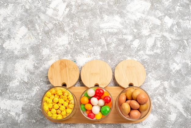 白い表面にさまざまなキャンディーのカラフルなお菓子の上面図