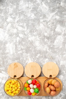 白い表面にさまざまなキャンディーのカラフルなお菓子の上面図 無料写真