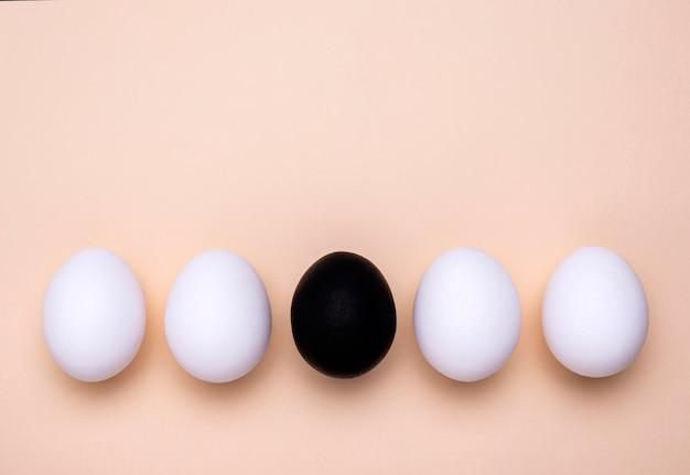 Вид сверху на яйца разного цвета для движения черной материи с копией пространства