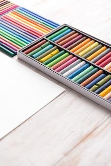 흰색 테이블에 상자에 다른 다채로운 파스텔 페인트와 마커의 상위 뷰