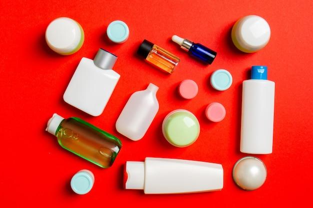 Вид сверху различных косметических бутылок и контейнера для косметики на цветном фоне. плоская композиция с копией пространства.