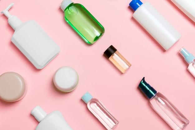 Вид сверху различных косметических бутылок и контейнера для косметики на розовом фоне. плоская композиция с копией пространства.