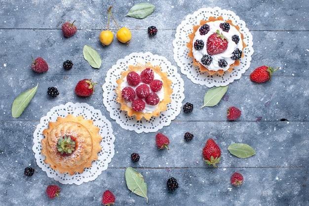 明るい机の上の新鮮な果物、ベリーの新鮮な果物と一緒にベリーとさまざまなクリーミーなケーキの上面図