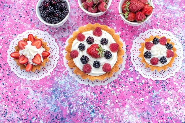 ライト、ベリーフルーツケーキビスケットにクリームと新鮮なベリーとさまざまなおいしいケーキの上面図