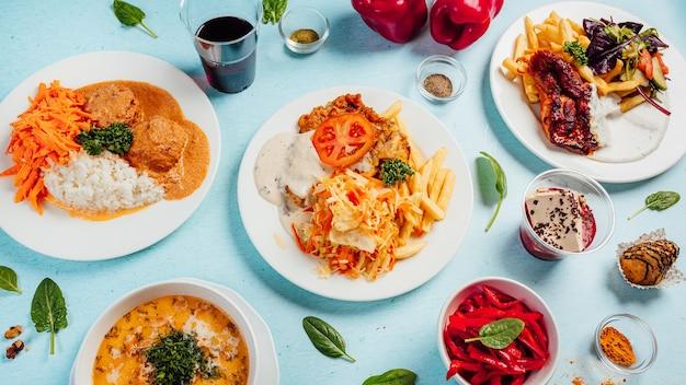 Вид сверху различных вкусных салатов с крем-супами и картофелем фри на столе
