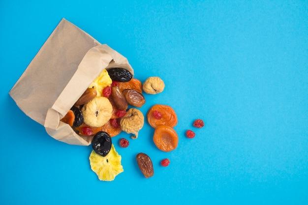 青い背景の上の紙袋にさまざまなドライフルーツの上面図