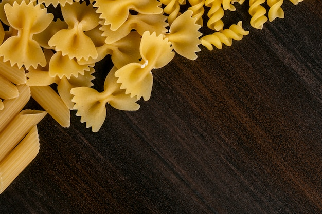 Вид сверху различной формы сырых макарон на деревянной поверхности