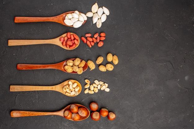 Вид сверху различных свежих орехов, арахиса и других орехов на темной поверхности