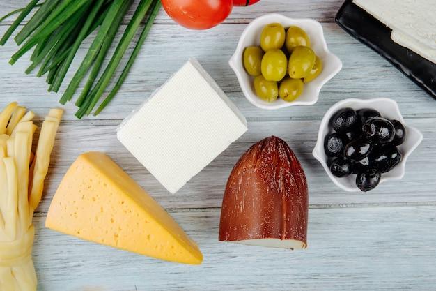 灰色の木製のテーブルにネギとオリーブのピクルスとさまざまな種類のチーズのトップビュー
