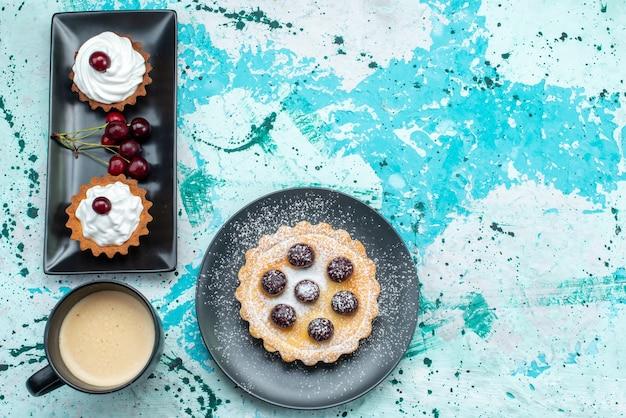 水色のケーキの甘い焼きクリームにクリームと新鮮なチェリーとさまざまな小さなケーキの上面図