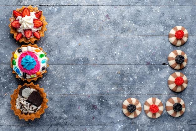 Вид сверху разных маленьких пирожных с нарезанными фруктами, конфетами, шоколадом и ягодами на сером, печенье, печенье, сладкое сахарное печенье